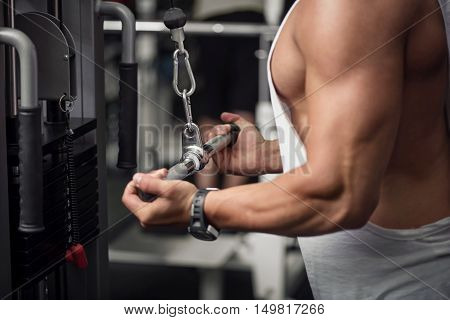 Intensive training. Strong athletic well built sportsman doing and exercise and developing his muscles while training