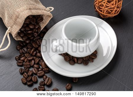 Empty cup of coffee with coffe beans as background