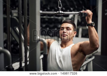 Physical strength. Hard working persistent man holding his hand up and pushing the weight while using a gym apparatus