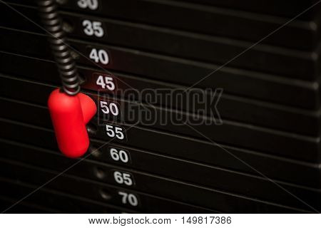 Sports equipment for bodybuilders. Close up of a black metal weight stack with a red plastic pin regulating weight