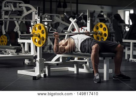 Immense strength. Young professional male weightlifter lying in a special position and preparing to lift a barbell while having a workout