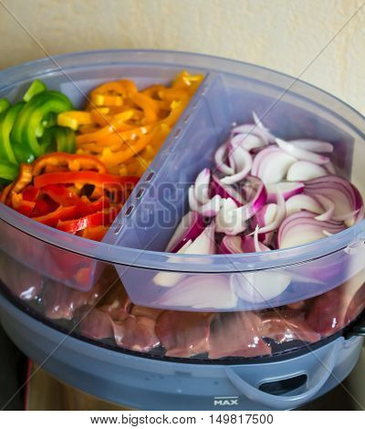 Healthy food cooking in steamer, steam cooker with green, yellow and red bell pepper, onion and chicken liver, selective focus