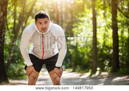 Long distance running. Pleasant tired young man bending forwards and touching his legs while running in the park
