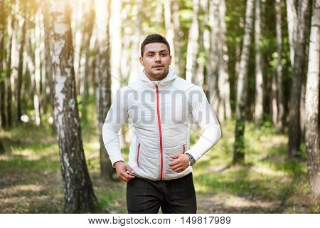 Good habit. Nice pleasant male runner looking forward and jogging while exercising in the park