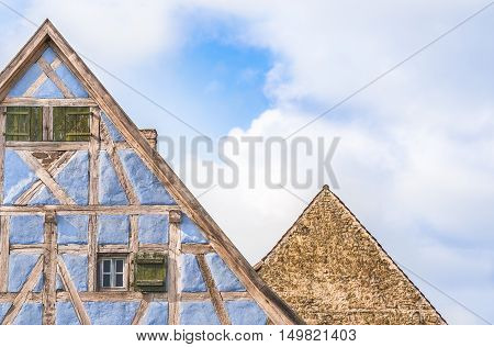 Two german house roofs against sky - Architectural details of two lofts from medieval german houses one with half timbered blue walls wooden shutters and one with stone wall.