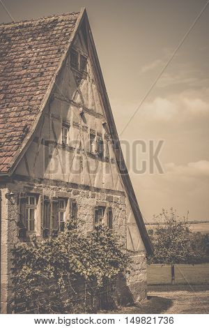 Vintage image of medieval german house - Retro style image of an antique german house with traditional architecture gable roof half timbered wall for the loft and stone wall wooden shutters and vine bushes for the ground floor.
