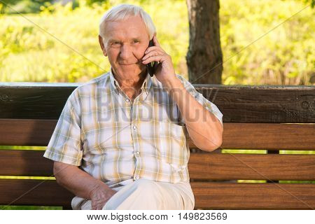 Smiling elderly man with phone. Senior male on a bench. I miss my relatives. Grandpa calls home.