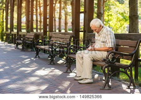 Elderly man with medicine bottle. Senior guy on park bench. I need some pills. Painkillers always at hand.