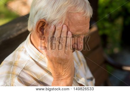 Senior man holds his head. Old person has headache. Pain is getting stronger. What a stressful day.