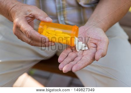Elderly hand holds pills. Orange tablet container. New type of antibiotics. Drug that suppresses pain.