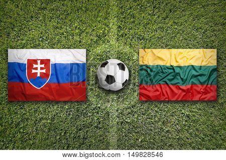 Slovakia vs. Lithuania flags on green soccer field, 3D illustration