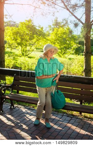 Elderly woman holding her stomach. Lady near park bench. Strong pain under ribs. Signs of chronic illness.