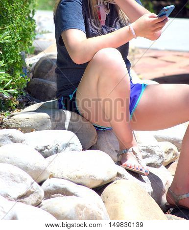Female beauty texting a friend outside on her cellphone.