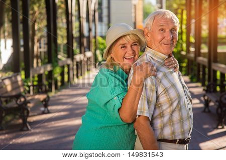 Senior woman is hugging man. Elderly couple smiling. Stay confident in each other. Time tests ties of love.