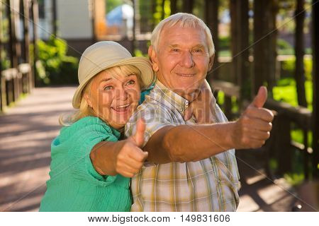 Elderly woman hugging man. Senior couple showing thumbs up. Loving hearts don't get tired. Many years spent together.