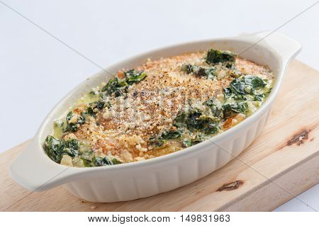 Modern style Spinach gratin (baked spinach with chesse) in ceramic bowl on wood plate