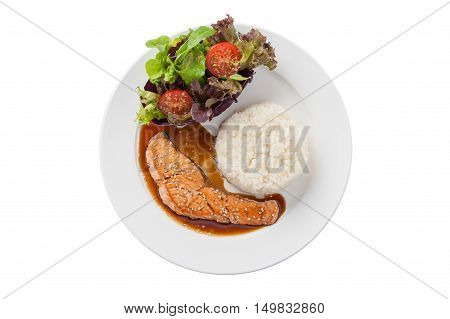 Top view of Fusion food style grilled salmon dressed with Japanese sweet sauce (Teriyaki) including Thai rice garnished with vegetables in ceramic dish isolated on white background