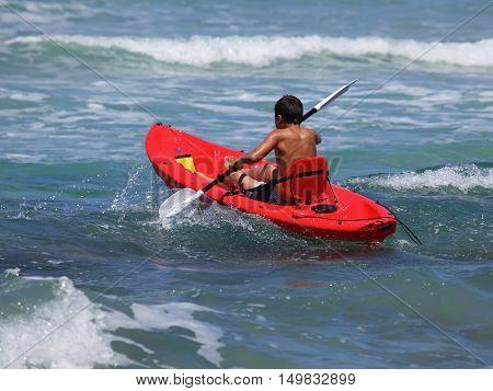 boy rowing in sea kayak.