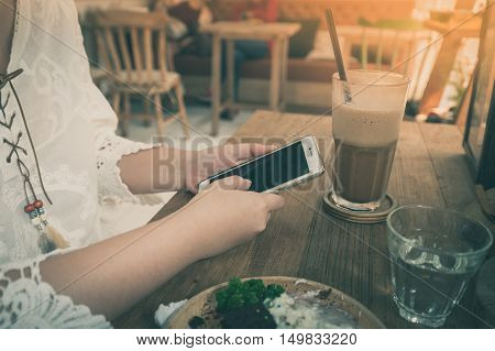 Weekend lifestyle scene of young woman using phone in cafe. Trendy lifestyle with technology concept with vintage filter effect
