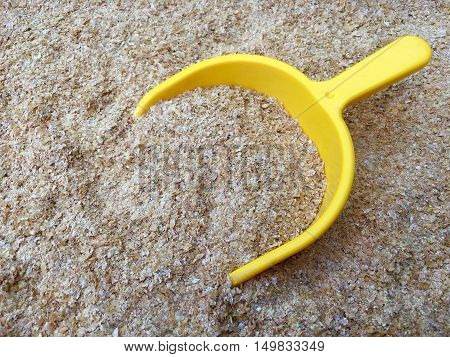 Wheat bran with a yellow shovel in closeup