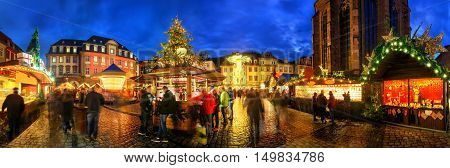 Christmas market in Heidelberg Germany a panorama shot at dusk showing illuminated kiosks architecture and blurred people