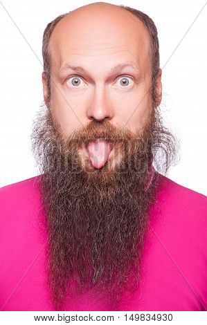 Portrait of a funny young bald bearded man showing tongue face expression
