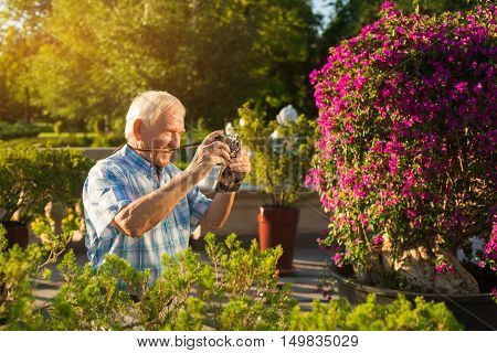 Senior man with camera. Elderly male outdoor. Grandpa found a new hobby. Impressive photos of nature. Few more pictures.