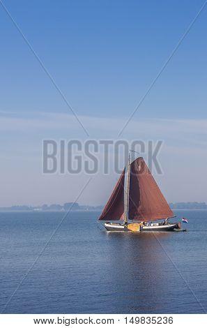 HOORN, NETHERLANDS - SEPTEMBER 13, 2016: Old wooden sailing boat on the Ijsselmeer near Hoorn, Netherlands