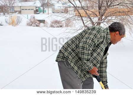 African american man shoveling winter snow outside.