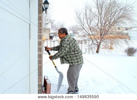 African american male shoveling winter snow outdoors.