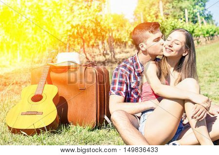 Young happy couple of lovers in tender moments on countryside - Handsome man whispers soft kisses in young woman ear - Love concept - Soft saturated filter with sun halo flare