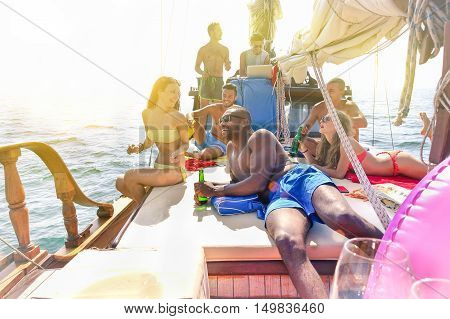Group of multiracial friends chilling and drinking beers in boat party - Young cheerful people cheering with beer bottles on sunny day - Concept about good and positive mood - Focus on black guy