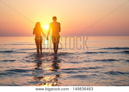 Silhouette of two lovers walking hand to hand on the beach at sunset time - Young people enjoying vacation holidays in summer - Concept of love relation and romantic moments - Original sun color tones