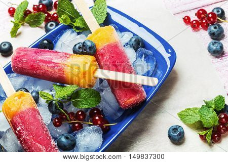 popsicles with red currants and blueberries on a wooden table