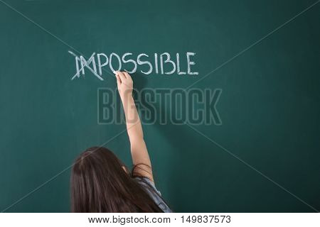 Little girl transforming word impossible  into possible on chalkboard
