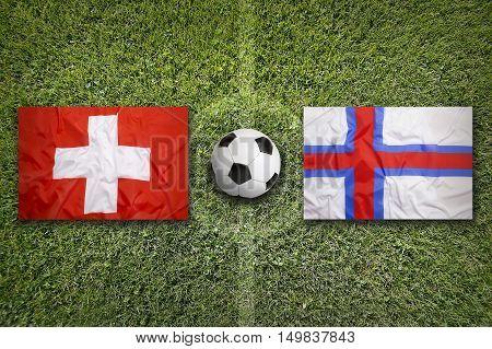 Switzerland vs. Faroe islands flags on green soccer field, 3D illustration