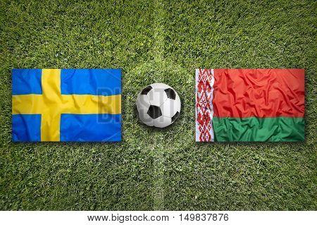 Sweden vs. Belarus flags on green soccer field, 3D illustration