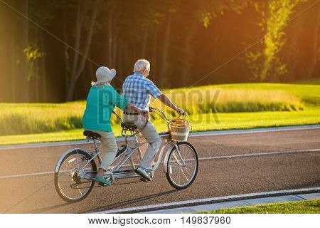 Senior couple on tandem bicycle. Bike on the road. Faster than wind. The racer inside me.