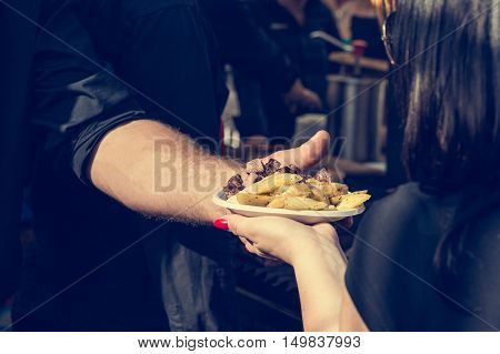 Chef serving potatoe dish to customer at outdoor stand. Street food photography.