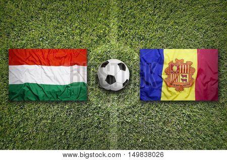 Hungary vs. Andorra flags on green soccer field, 3D illustration