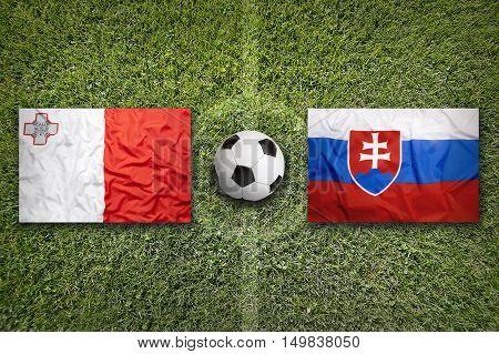 Malta vs. Slovakia flags on green soccer field, 3D illustration
