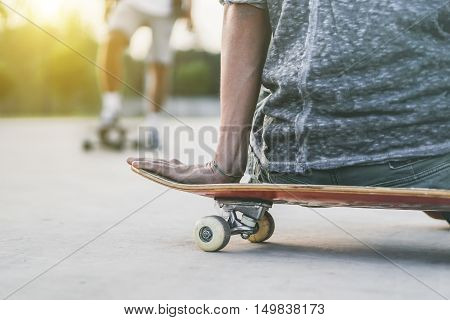 Closeup of young man sitting on skateboard looking his friend training outdoor - Skateboarder preparing to jump in urban contest - Extreme sport concept - Focus on hand - Vintage desaturated filter
