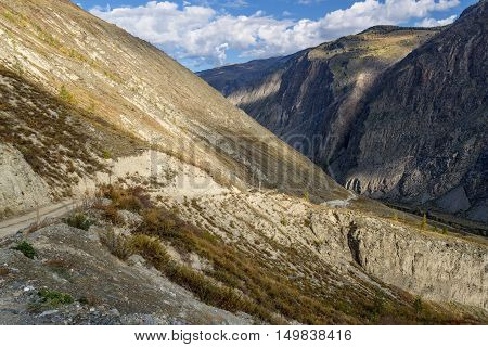 Scenic view of steep winding gravel mountain road through the pass part of the mountain serpentine passing the of the mountain on a background of blue sky and clouds