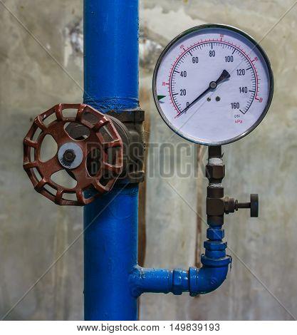 Valve and Water pressure gauge meter. on wall background