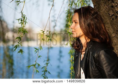 Cute girl contemplating leaning against a tree