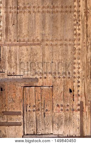 old wooden door with rusty rivets and fittings