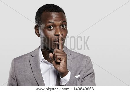 Dark-skinned Entrepreneur In Gray Suit Holding Finger On His Lips, Asking To Keep Confidential Infor