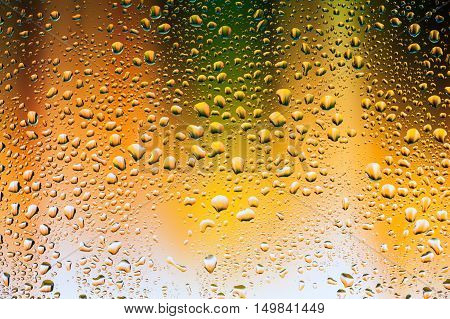 Abstract texture - Water drops on glass with yellow and green background