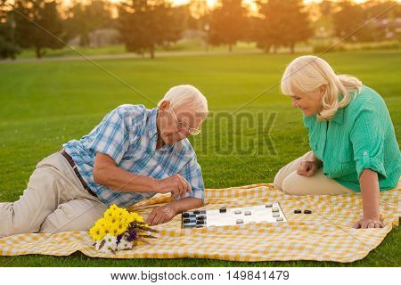 Senior couple playing checkers. Blanket on the meadow. Smart move, darling. I know your weaknesses.