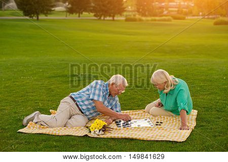 Senior couple is playing checkers. Two people on lawn. Think before you move. Strategy of the wise.